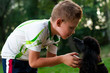 boy with a black poodle on nature