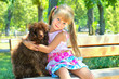 Little girl hugging a poodle dog